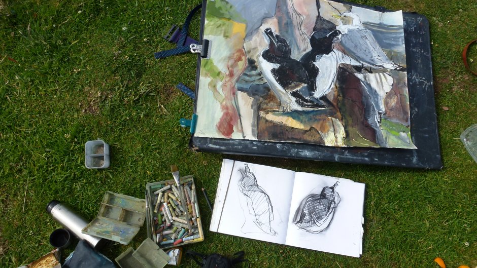 Artist set up working outdoors, drawing, sketches and materials laid on grass