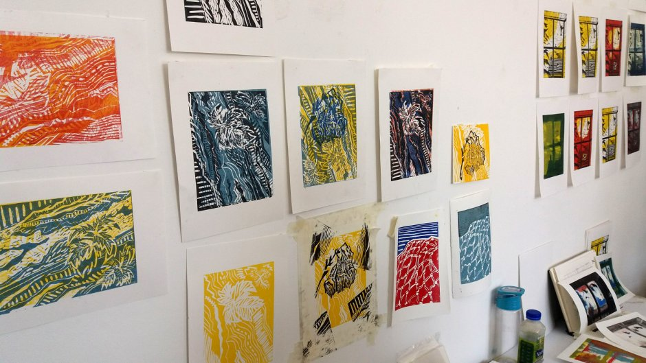 Colourful lino cut prints hanging on a wall
