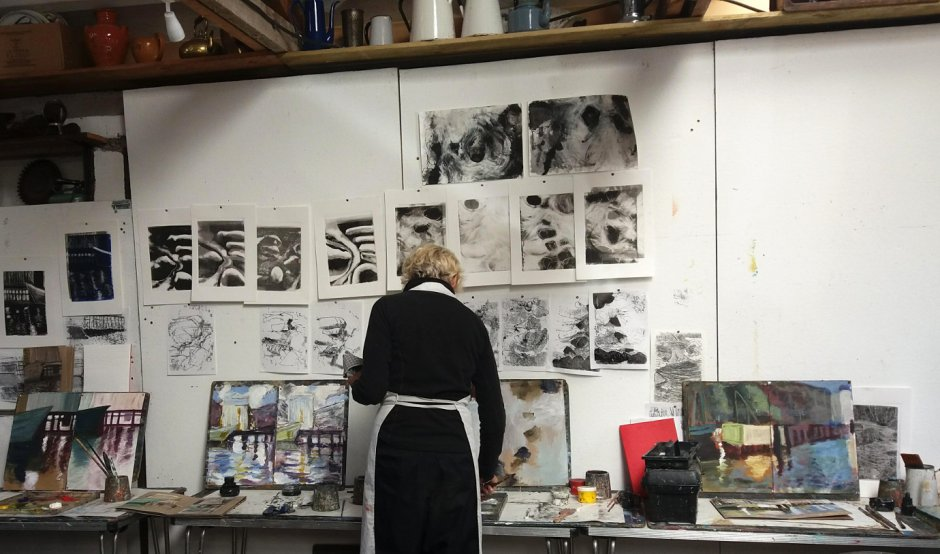 Woman working in front of a busy studio wall covered in abstract monochrome prints